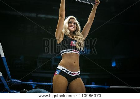beautiful young girl smiling in ring, shows a sign with round number