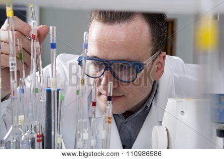 Male Scientist With Laboratory Pipettes