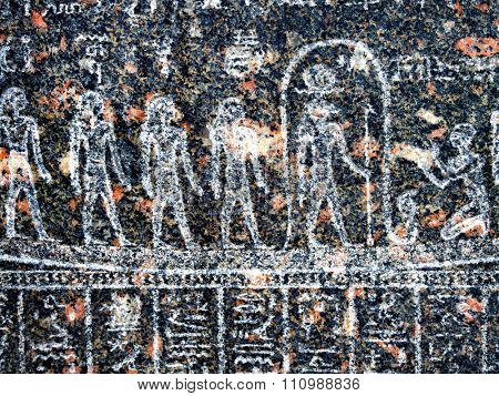 Ancient egyptian hieroglyph depicting human figures carved in black granite stone