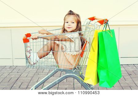 Happy Smiling Child Sitting In Trolley Cart With Colorful Shopping Bags Having Fun
