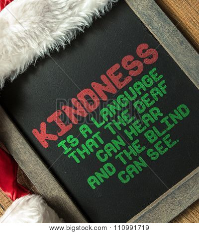 Kindness Is a Language That the Dead Can Hear And The Blind Can See written on blackboard with santa hat