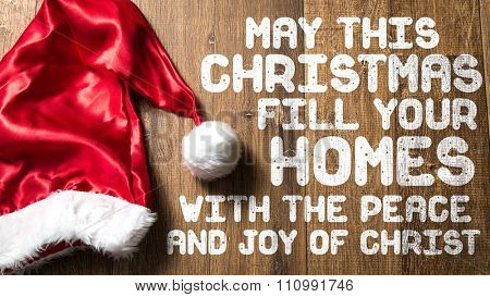 May this Christmas Fill Your Homes With the Peace and Joy of Christ written on wooden with Santa Hat