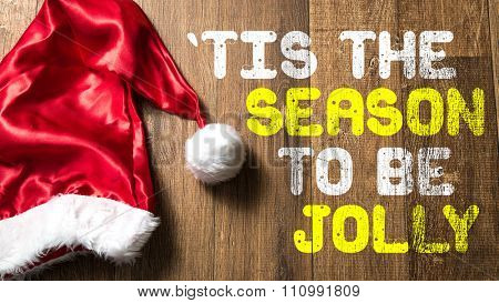 'Tis The Season To Be Jolly written on wooden with Santa Hat