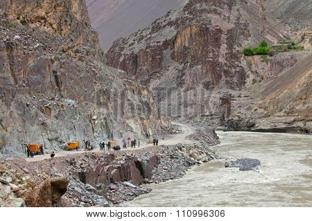 SRINAGAR â?? LEH ROAD, JAMMU & KASHMIR, INDIA - JUNE 11, 2015:  Bulldozer doing mountain road repair and construction works after landslide  in Himalayas