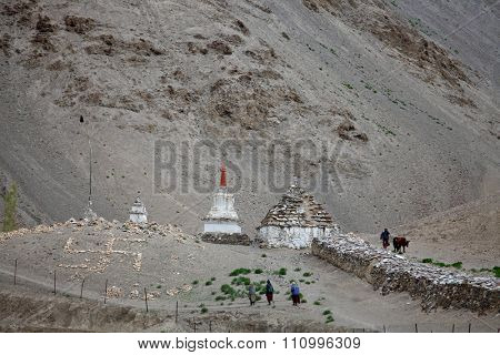 LAMAYURU,  JAMMU & KASHMIR, INDIA - JUNE 02, 2015: Pilgrims going to stupas and stone swastika cross (Buddhist symbols) in the Himalayas â?? near Lamayuru monastery in Ladakh province