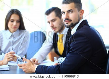 Happy young businessman in business meeting at office, looking at camera smiling.