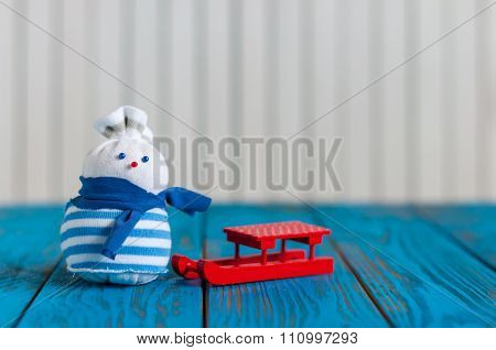 Red sled and little handmade snowman on light wooden background. Xmas card with empty space for text