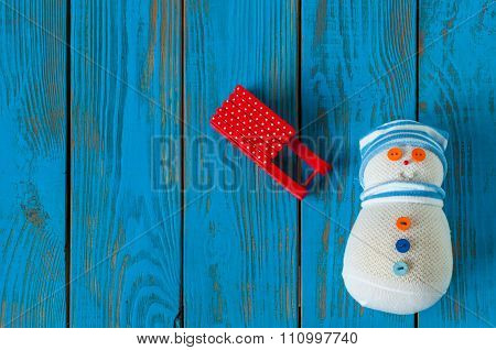 Red sled and handmade snowman on blue wooden background. Xmas card with empty space for text. Unique