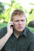 image of angry man  - young man on a cellphone gets bad news - JPG