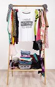 Many Clothes On The Rack With A T-shirt Saying Nothing To Wear. poster