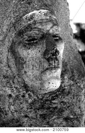 Scary Face Carved In Granite At A Cemetery Gravesite
