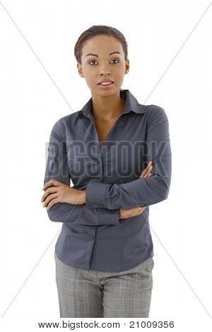 Young pretty businesswoman posing with arms folded in studio, looking at camera,?