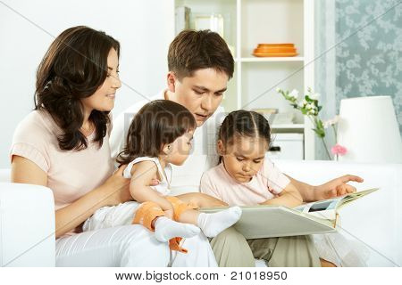 Portrait of happy family with two children sitting at home and reading book