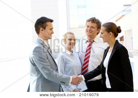 Portrait of two business partners handshaking after making agreement with two employees near by