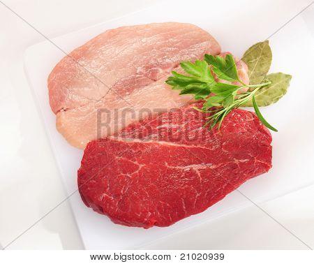 Raw Pork Chop And Steak. Arrangement On A White Cutting Board.
