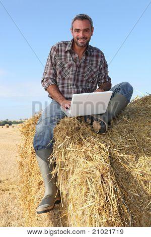 granjero, sentado en la computadora bale y haciendo paja