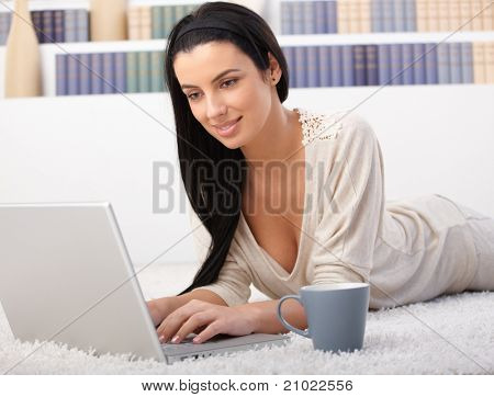 Woman browsing internet on laptop computer at home, lying on living room floor.?