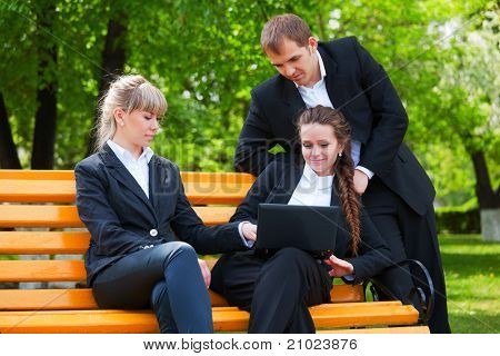 Young business people with laptop on the bench