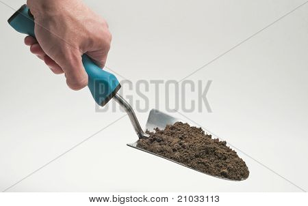 Using garden trowel with dirt