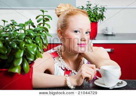 girl with cup of morning coffee in interior of kitchen