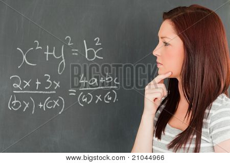 Pensive Cute Woman Trying To Solve An Equation