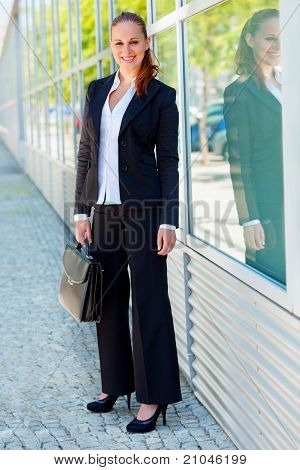 Full length portrait of smiling modern business woman with briefcase at office building