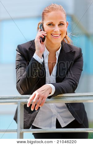 Portrait of smiling modern business woman leaning on railing and talking on mobile