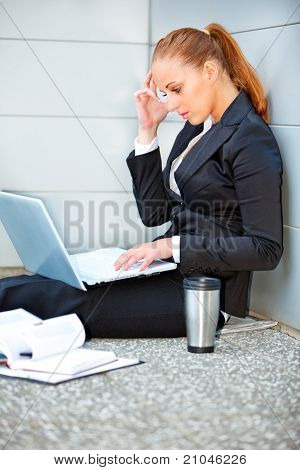 Concentrated modern business woman sitting on floor at office building and using laptop