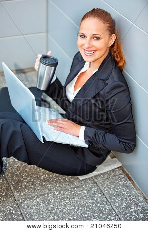 Smiling modern business woman with laptop and cup sitting on floor at office building