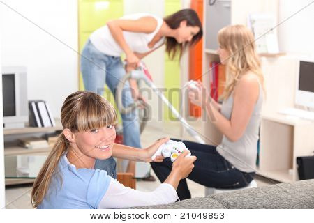 a woman vacuuming and two women playing video games