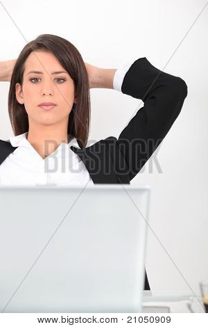 Woman leaning back from her laptop computer
