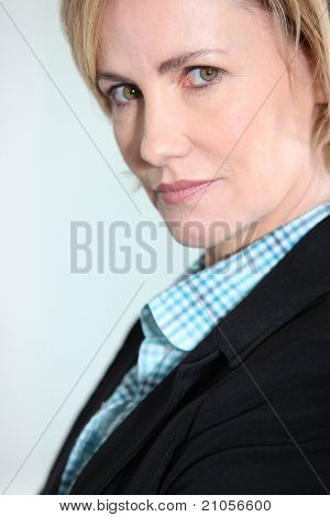 Head and shoulders studio shot of an intense woman in a suit jacket