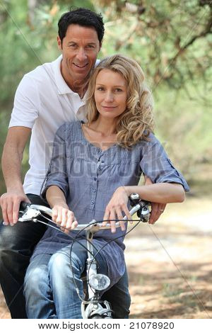 Couple riding bike in forest