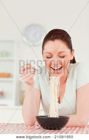 Beautiful woman posing while eating pasta in her kitchen