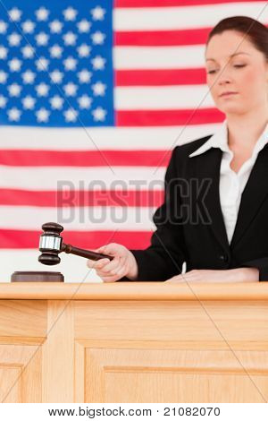 Portrait of a focused judge knocking a gavel with the camera focus on the gavel