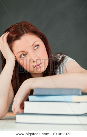 Beautiful bored student with her forearm on her books in a classroom