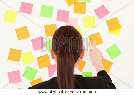 Red-haired woman taking a re-positional notes on a white wall