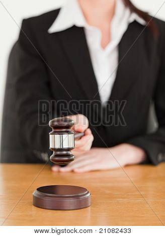 Young woman using a gavel while sitting at a desk against a white background