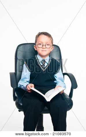 The boy sits and reads the book