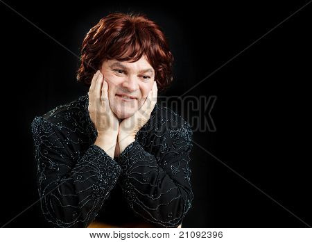 Man dressed as celebrity female entertainer.  Black background.