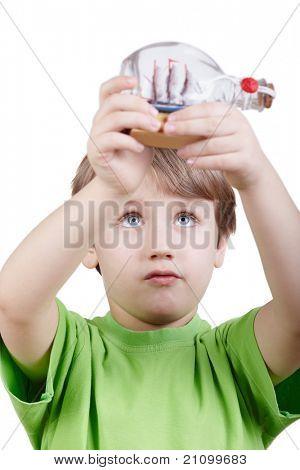 Menino em t-shirt verde olha para o modelo em miniatura de um tallship na garrafa possui em seu um