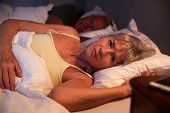 Worried Senior Woman In Bed At Night Suffering With Insomnia poster