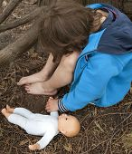 stock photo of child abuse  - Young and sad child with a doll hiding under a tree - JPG