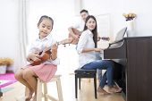 Asian Family,daughter Playing Ukulele,father Playing Guitar,mother Playing Piano poster