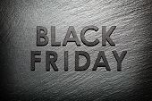 Black Friday text on black slate background poster