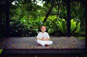 Cute Little Baby Boy, Kid Meditating In Rainy Forest Park, Sitting On Wooden Decks poster