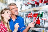 Employee of hardware store helping customer in ironware department with fittings poster