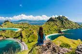 Rear view of a young woman enjoying the awesome view of Padar Island, while sitting on the top of a  poster