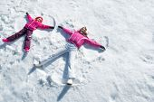 Cheerful mother and daughter enjoying in snow while looking at camera. Happy woman with little child poster