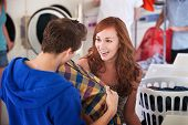 foto of laundromat  - Young lady smiles as a man holds a shirt in the laundromat - JPG